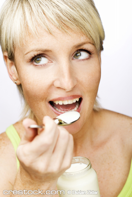 young beautiful woman eating yogurt close up
