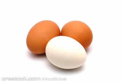Three chicken eggs on a white background largly
