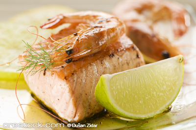 Grilled salmon and prawn with lime close up