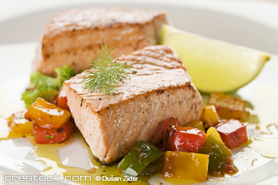 Grilled salmon steak with vegetables close up
