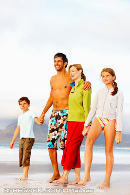 Beach vacation - Family of four taking a strol...