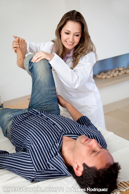 physiotherapist doing therapy to a man on his leg
