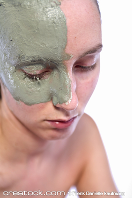 Nude woman model with a partial clay mask