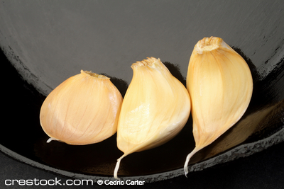 Three Cloves of garlic in a cast iron skillet.