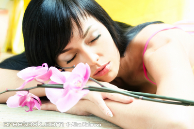 Beautiful asian girl with orchid. Low DOF, foc...